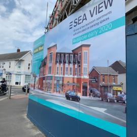 Image of hoarding and artists impression of new building
